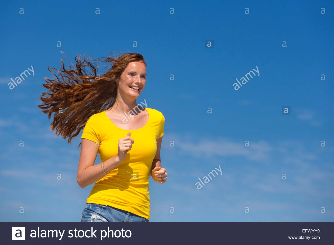 Smiling woman running with blue sky background - Stock Image