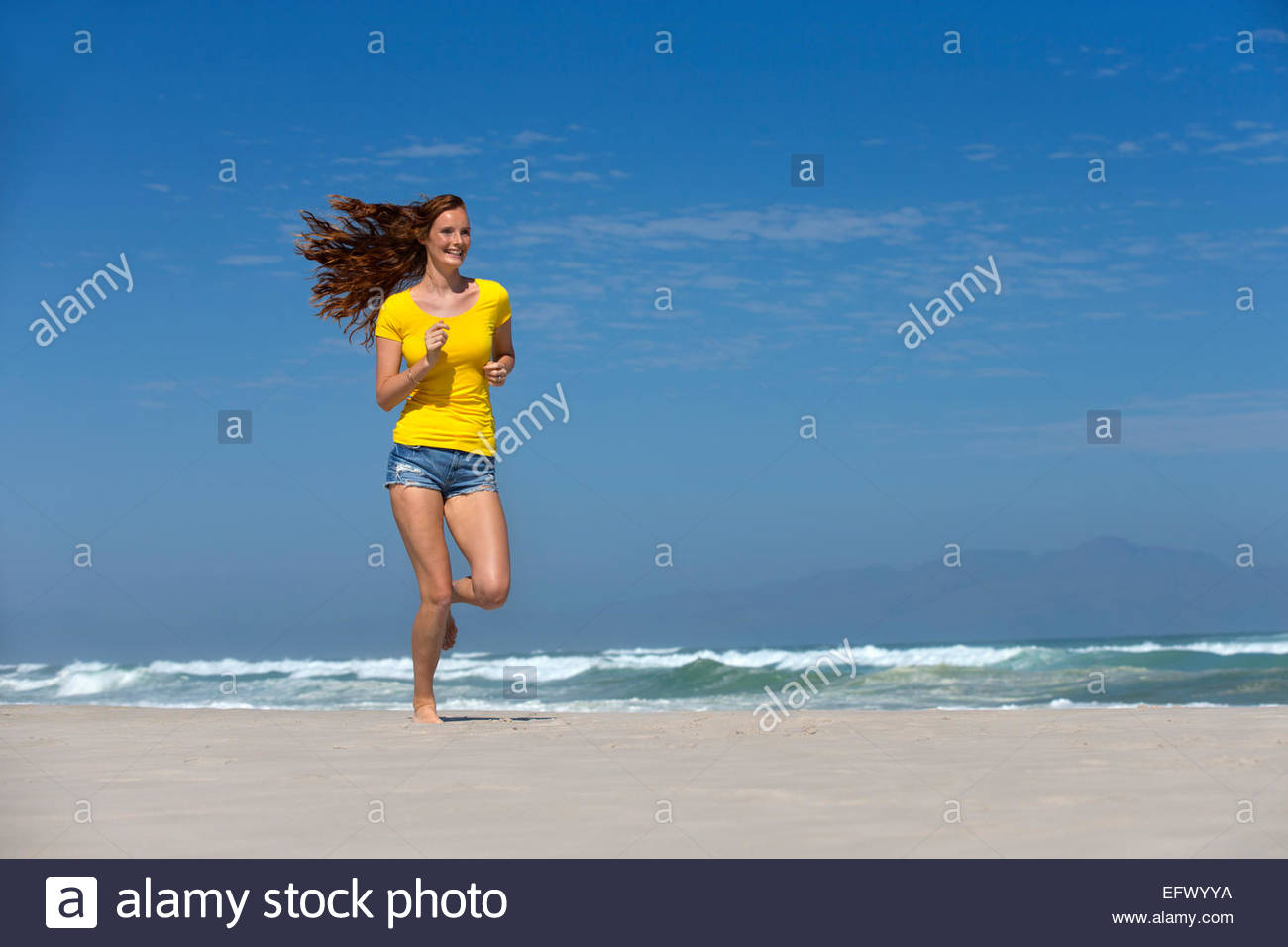 Smiling woman running on sunny beach - Stock Image