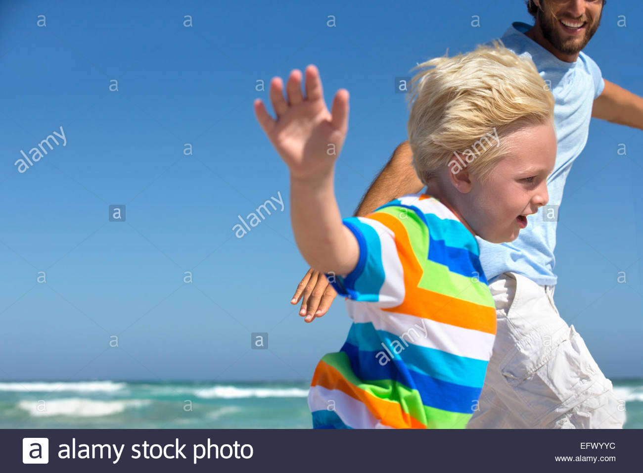Smiling Father and son, with arms outstretched, running on sunny beach - Stock Image