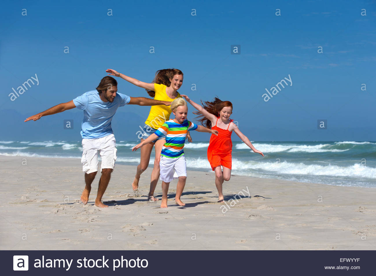 Happy family, pretending to fly, running on sunny beach - Stock Image