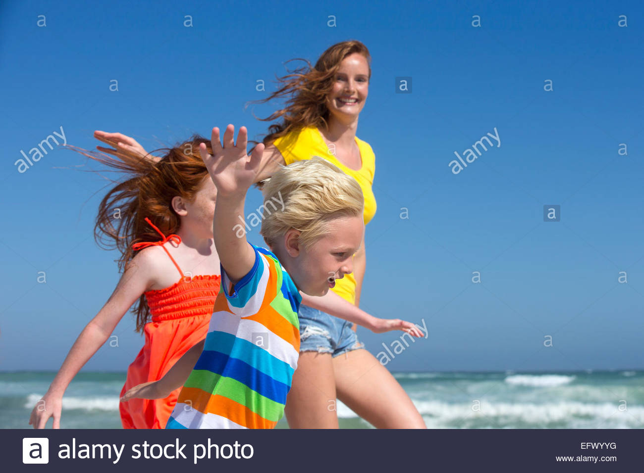 Mother, daughter and son, arms outstretched, running on sunny beach - Stock Image