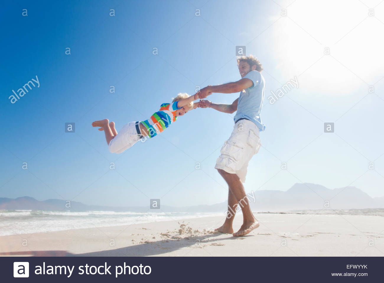 Smiling Father swinging son around playfully on sunny beach - Stock Image