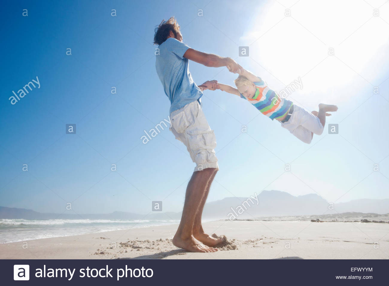 Father swinging son in the air playfully on sunny beach - Stock Image