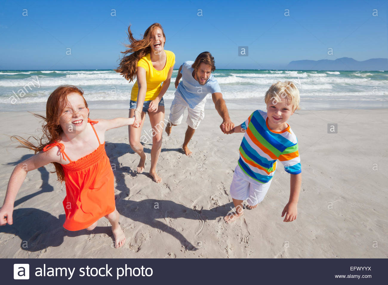 Happy family smiling at camera, holding hands, on sunny beach - Stock Image