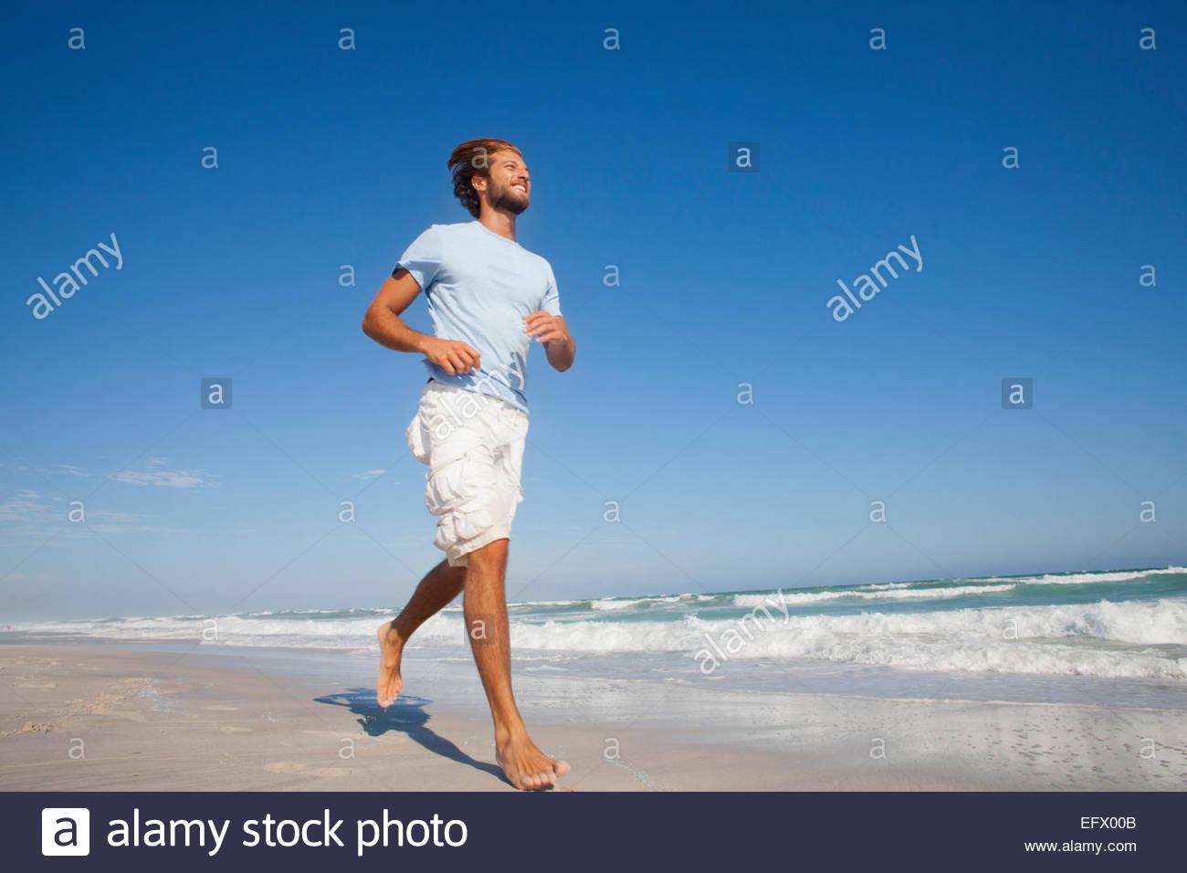 Smiling Man running on sunny beach - Stock Image