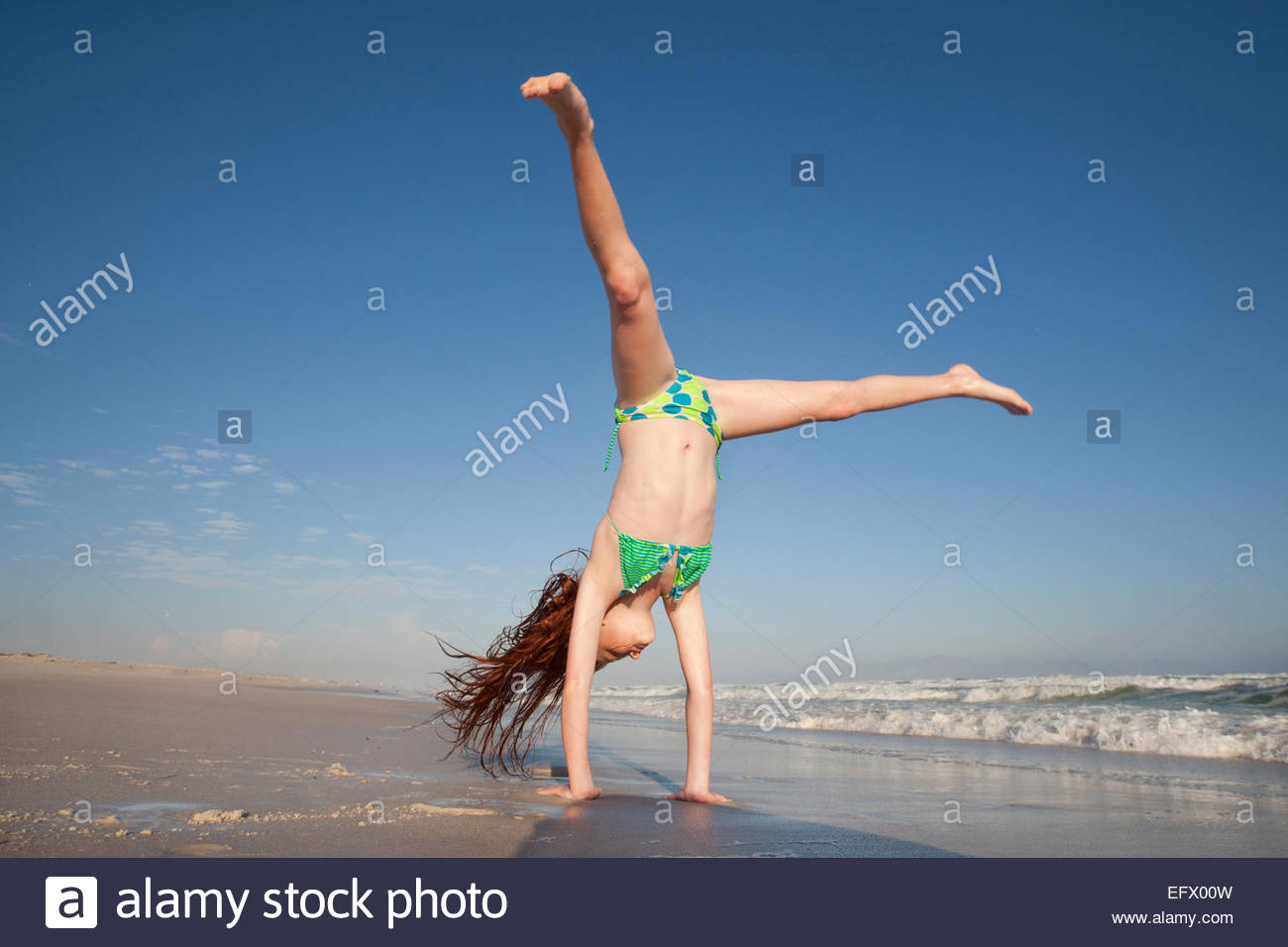 Redheaded Girl doing handstand on sunny beach - Stock Image