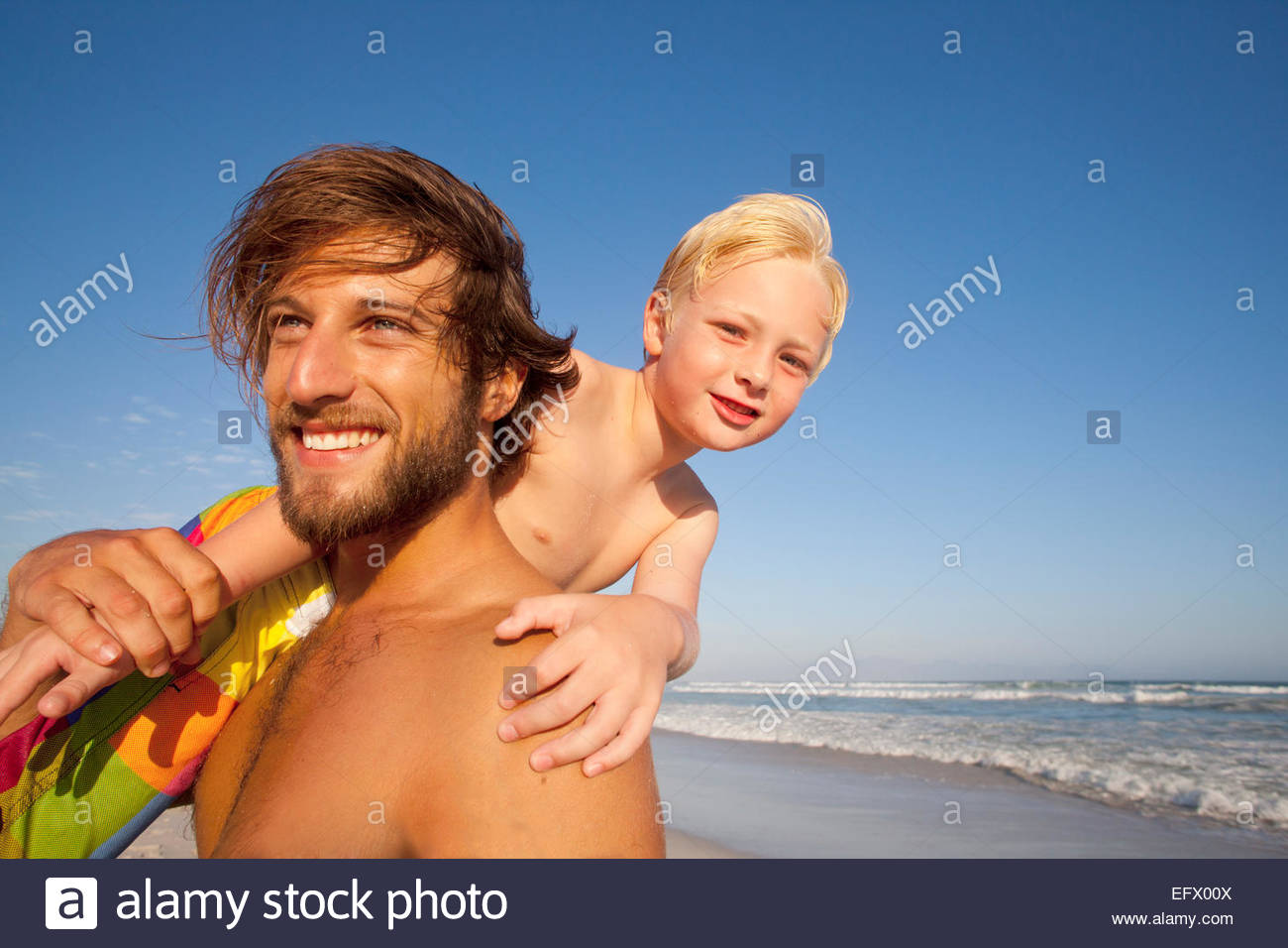 Smiling father, holding son on shoulder, on sunny beach - Stock Image