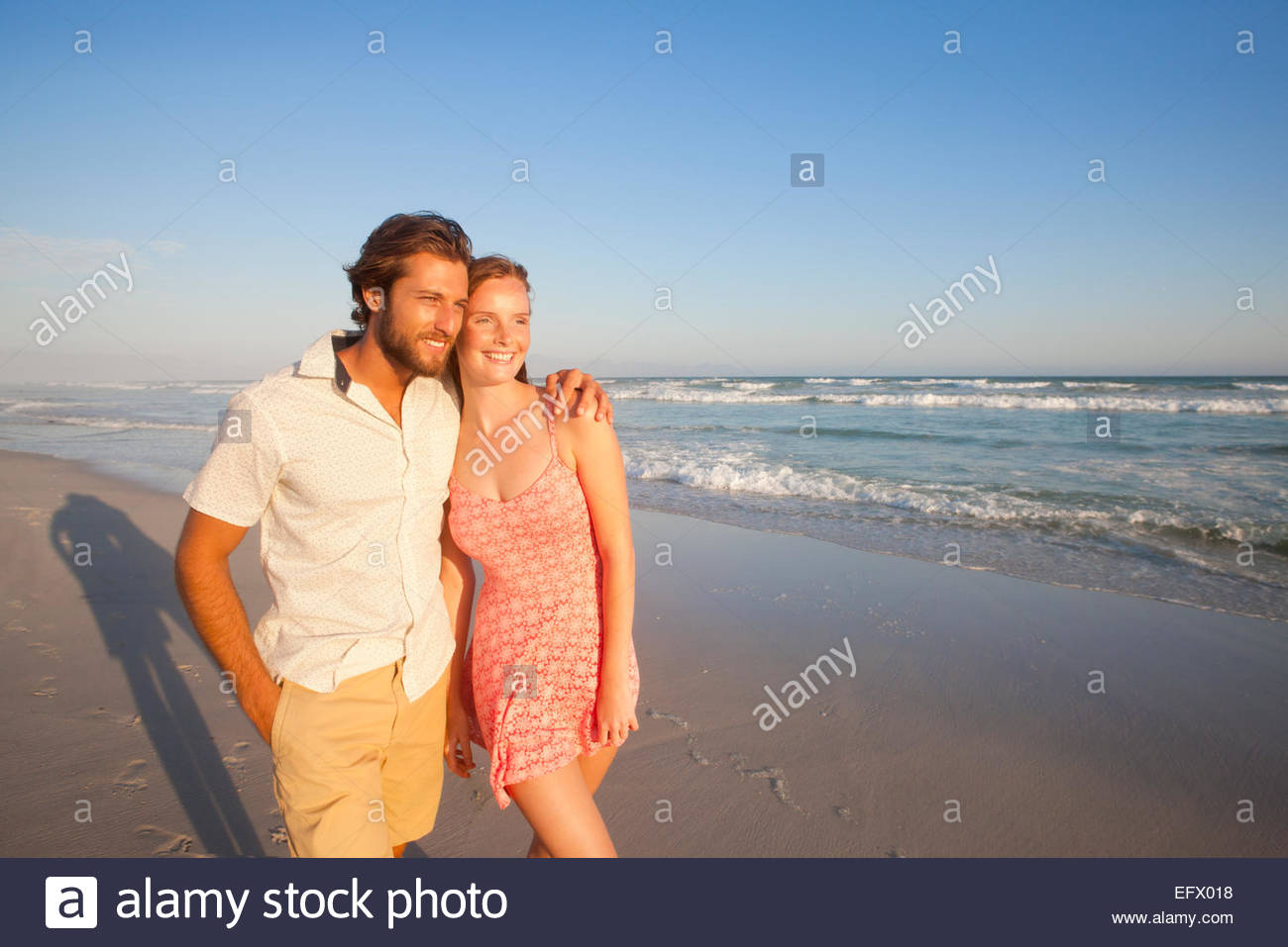 Smiling couple, man with arm round woman, walking along sunny beach - Stock Image