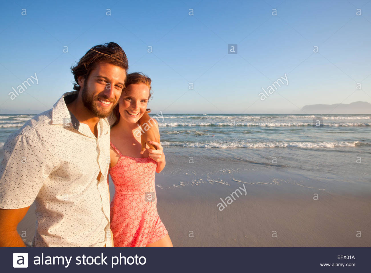 Smiling couple looking at camera, man with arm round woman, walking along sunny beach - Stock Image