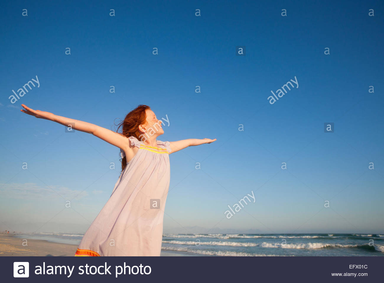 Happy girl, with arms raised to the sky, on sunny beach - Stock Image