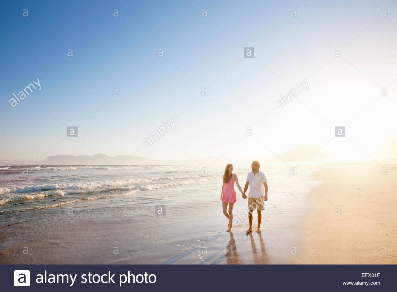 Couple, holding hands, walking along sunny beach - Stock Image