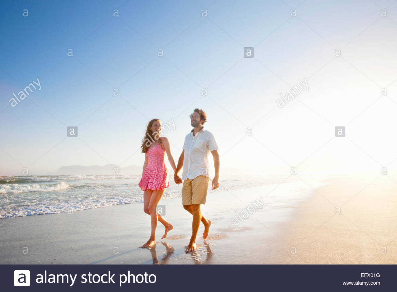 Smiling couple, holding hands, walking along sunny beach - Stock Image