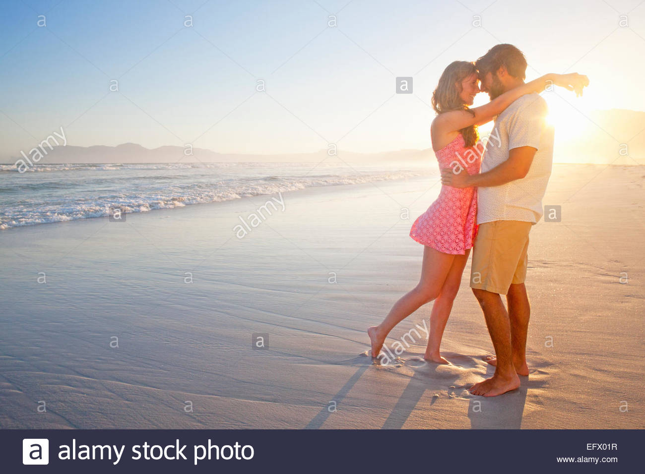 Romantic couple embracing, about to kiss, on sunny beach - Stock Image