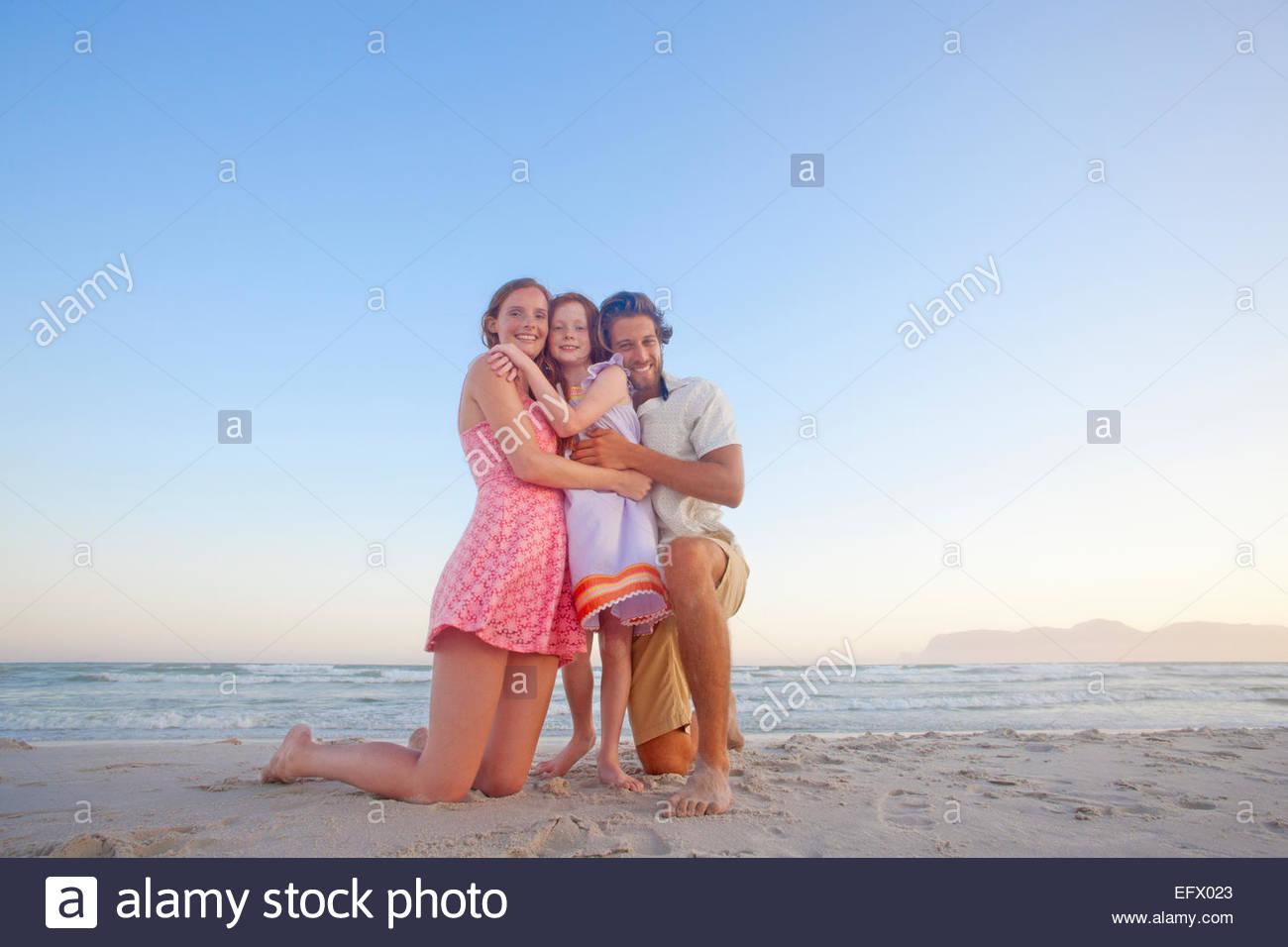 Happy couple kneeling, hugging daughter, on sunny beach - Stock Image
