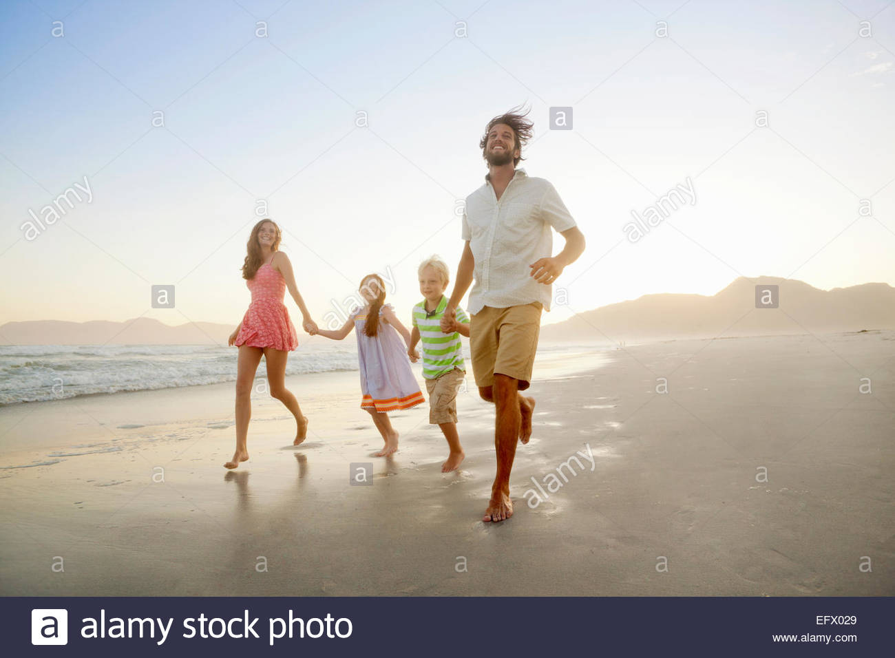 Happy family, holding hands, running on sunny beach - Stock Image