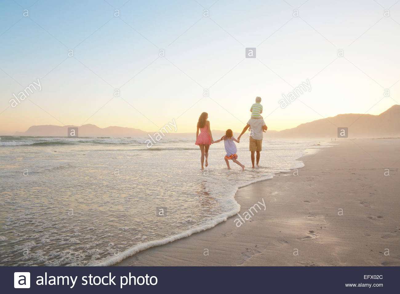 Happy family walking into distance, holding hands and son having piggy-back, on sunny beach - Stock Image