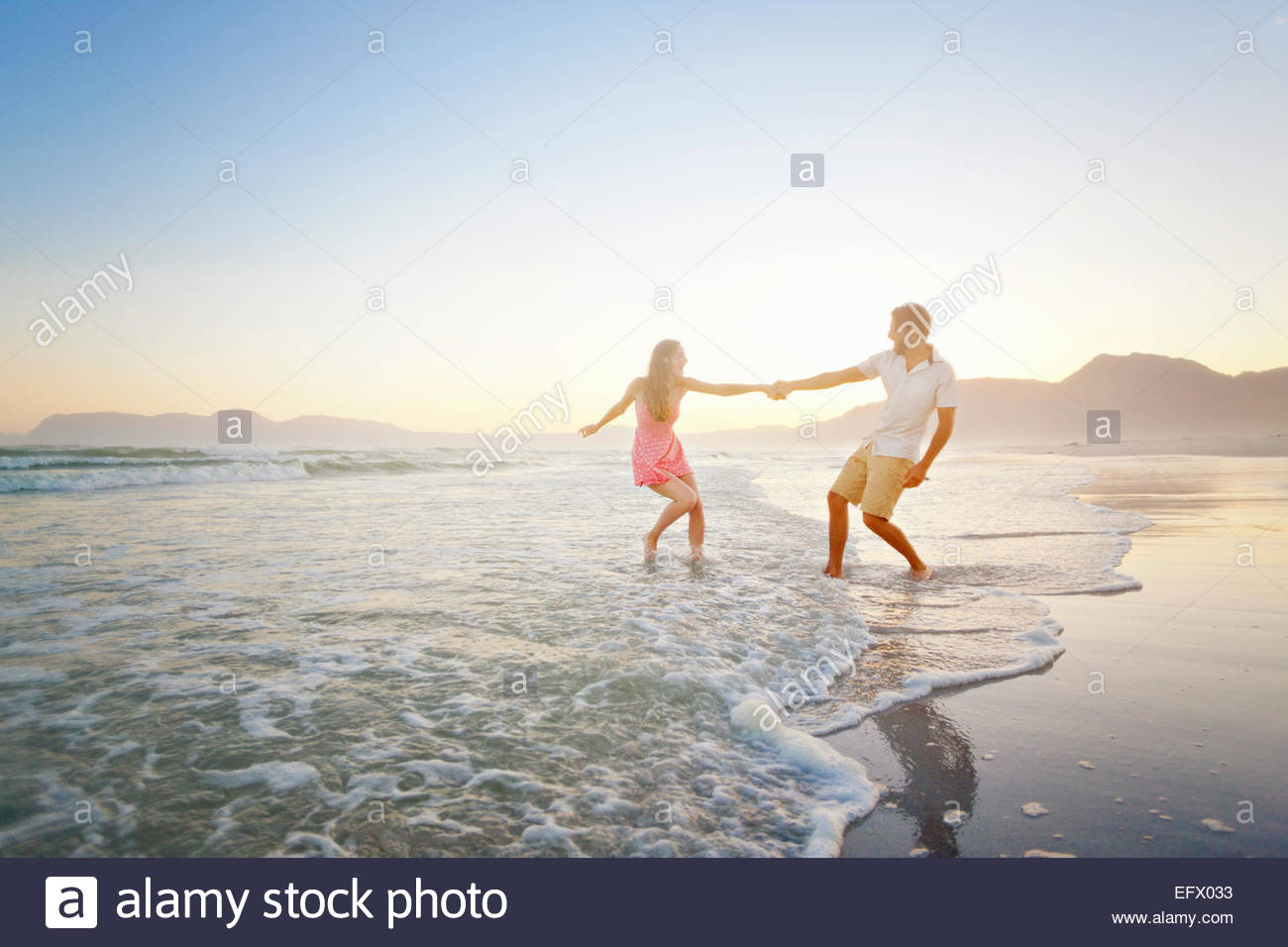 Couple, holding hands, playfully walking through waves on sunny beach - Stock Image