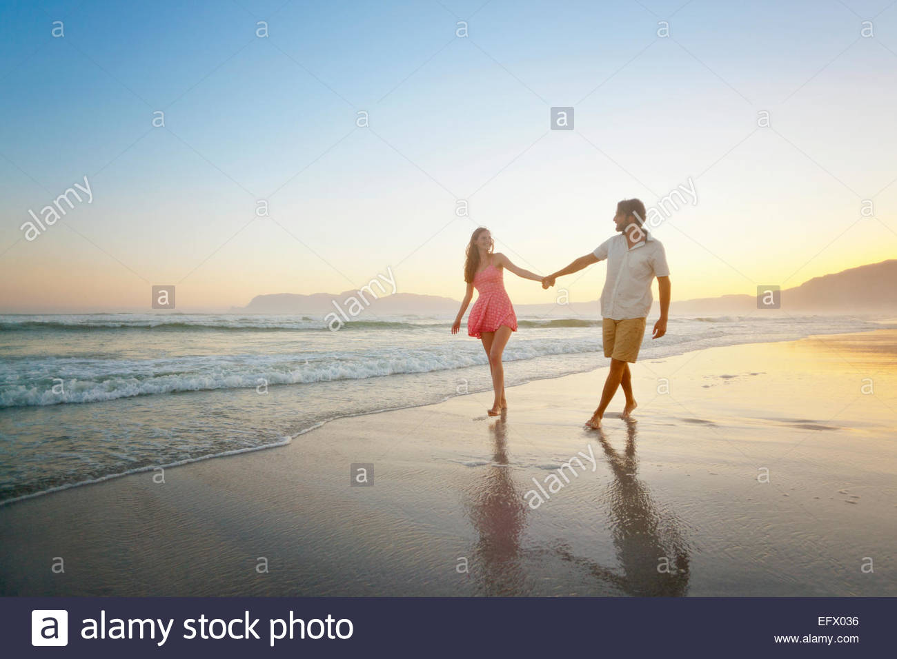Couple, holding hands, walking along sunny beach Stock Photo