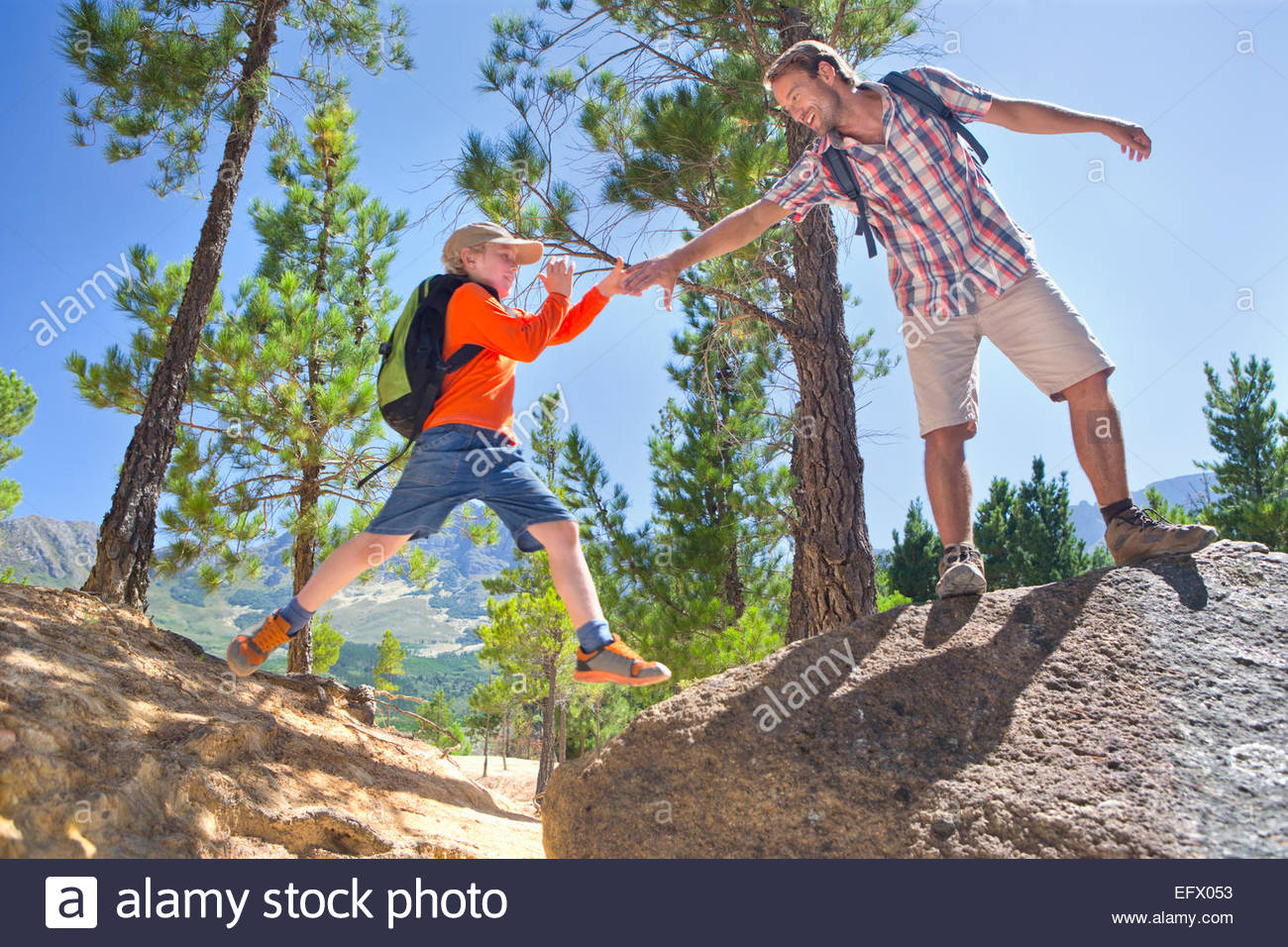 Father helping son climb, on mountain path - Stock Image