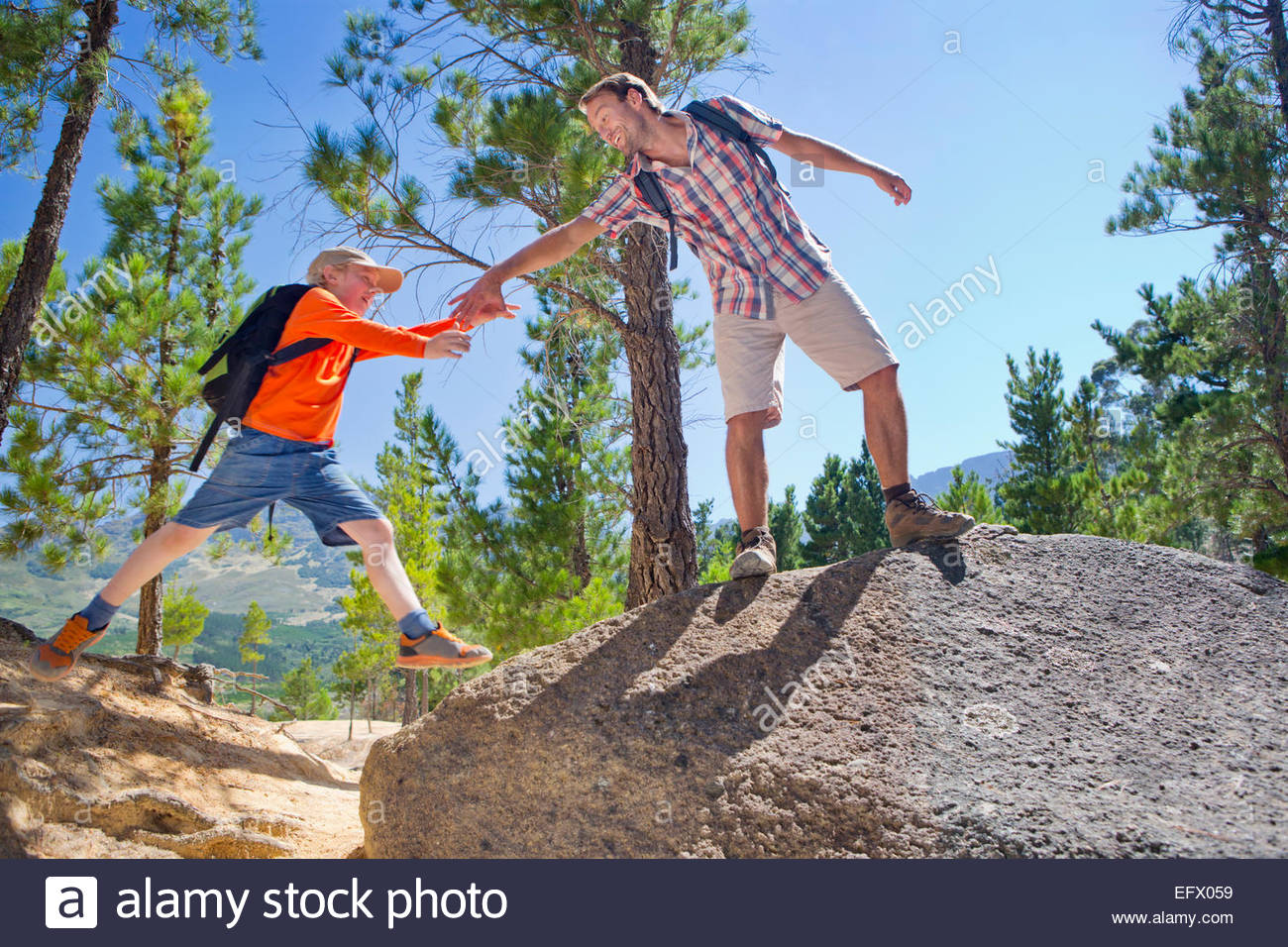 Father helping son climb on mountain path - Stock Image