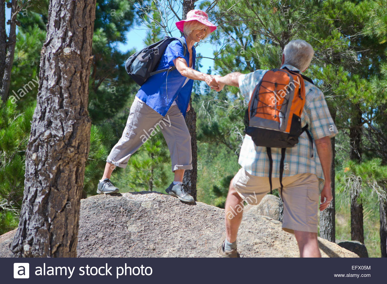 Senior couple helping each other hiking on mountain path - Stock Image