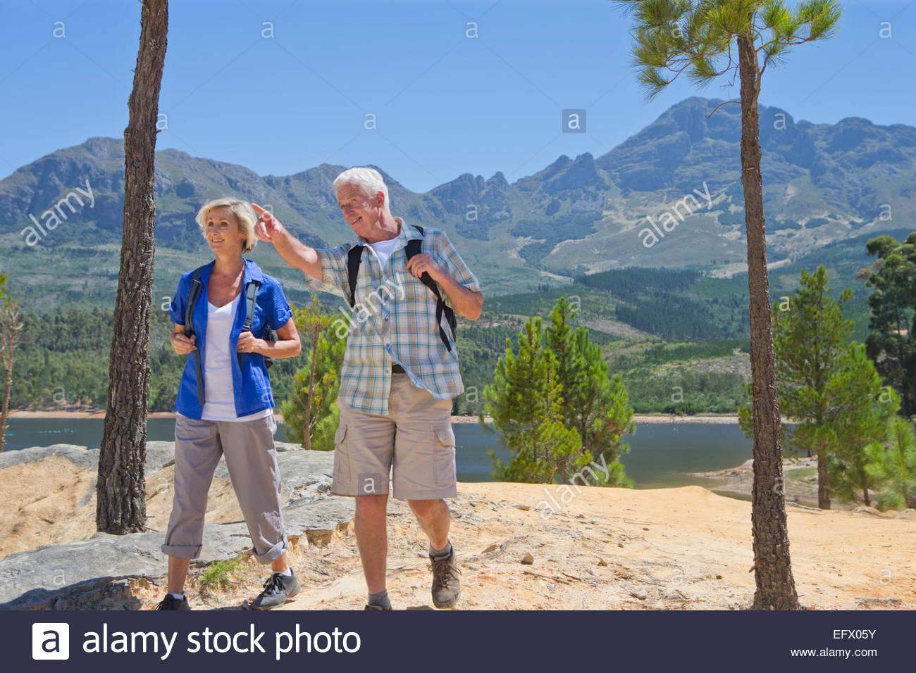 Senior couple hiking on mountain path next to lake - Stock Image