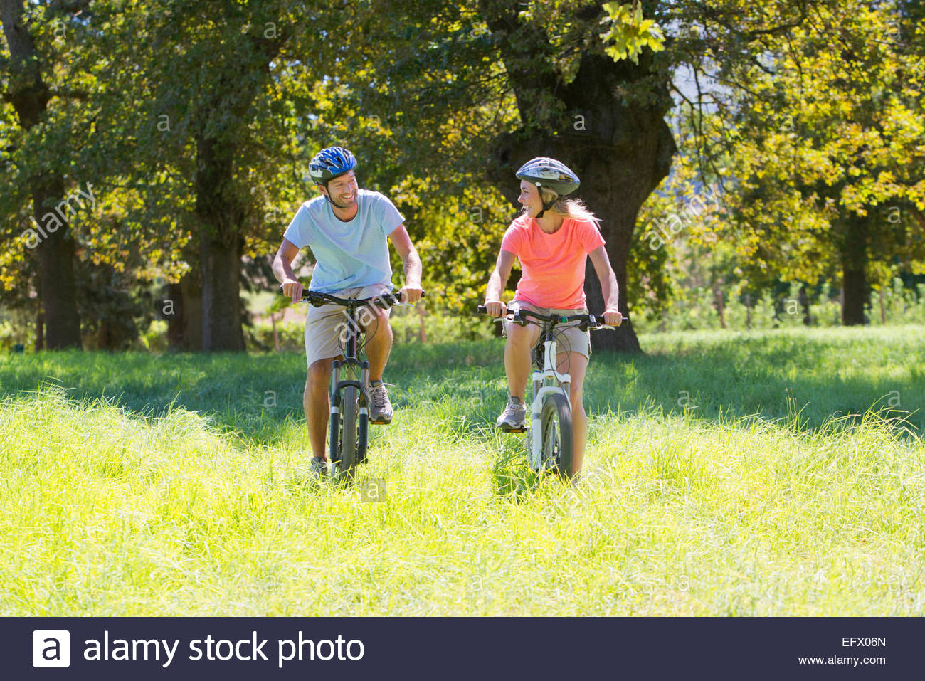 Couple, mountain biking, in treelined field - Stock Image
