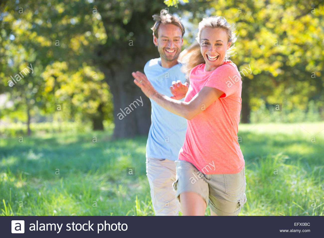 Couple, playfully chasing each other, in treelined field - Stock Image