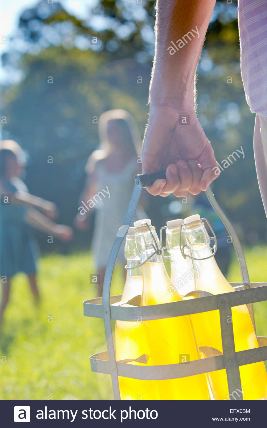 Close up of man carrying crate with bottles of juice, with family playing in distance Stock Photo