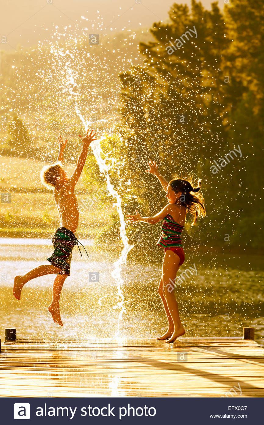 Young boy and girl jumping in air on jetty through splash of water - Stock Image