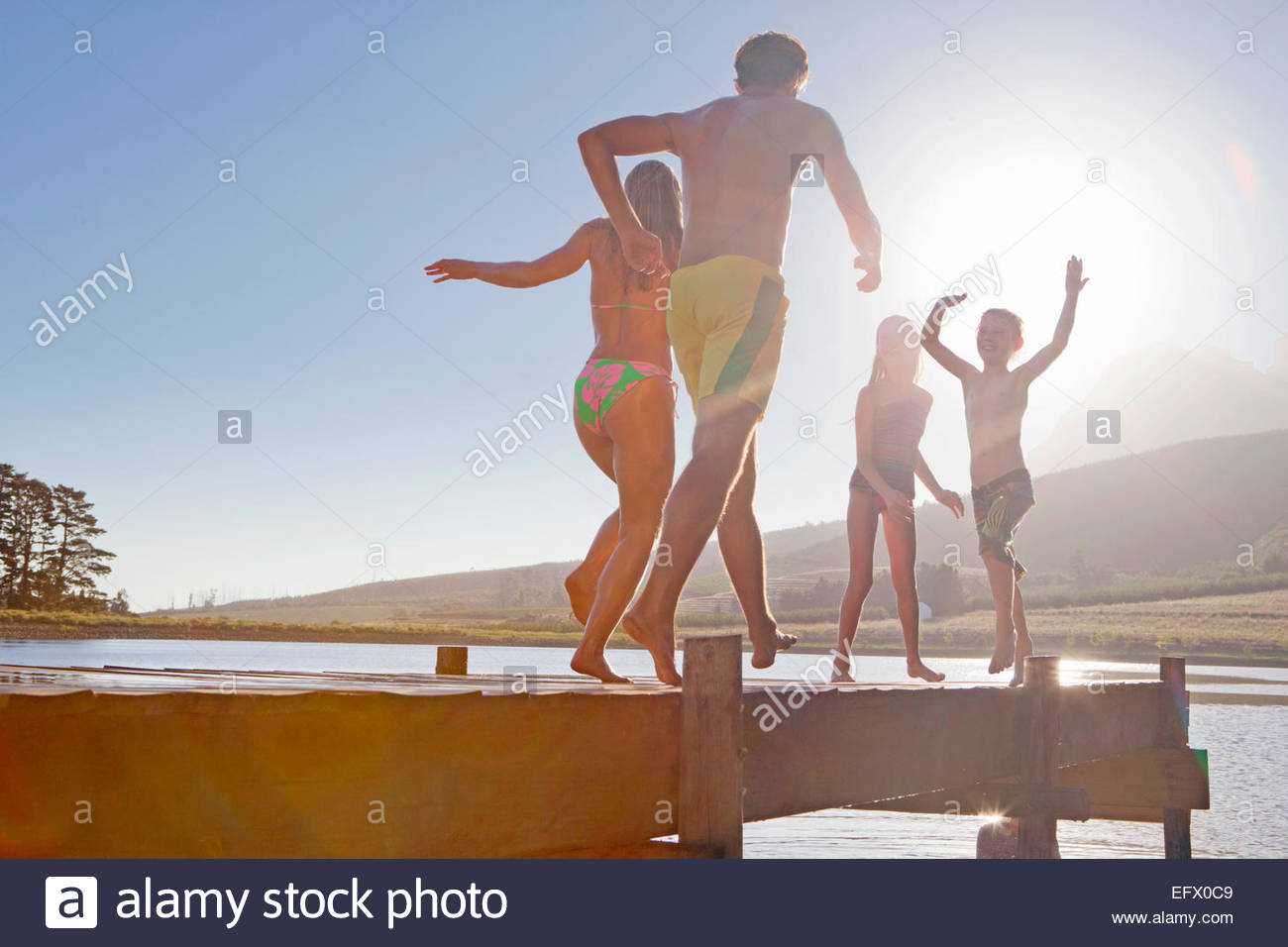 Happy family running and jumping on jetty - Stock Image