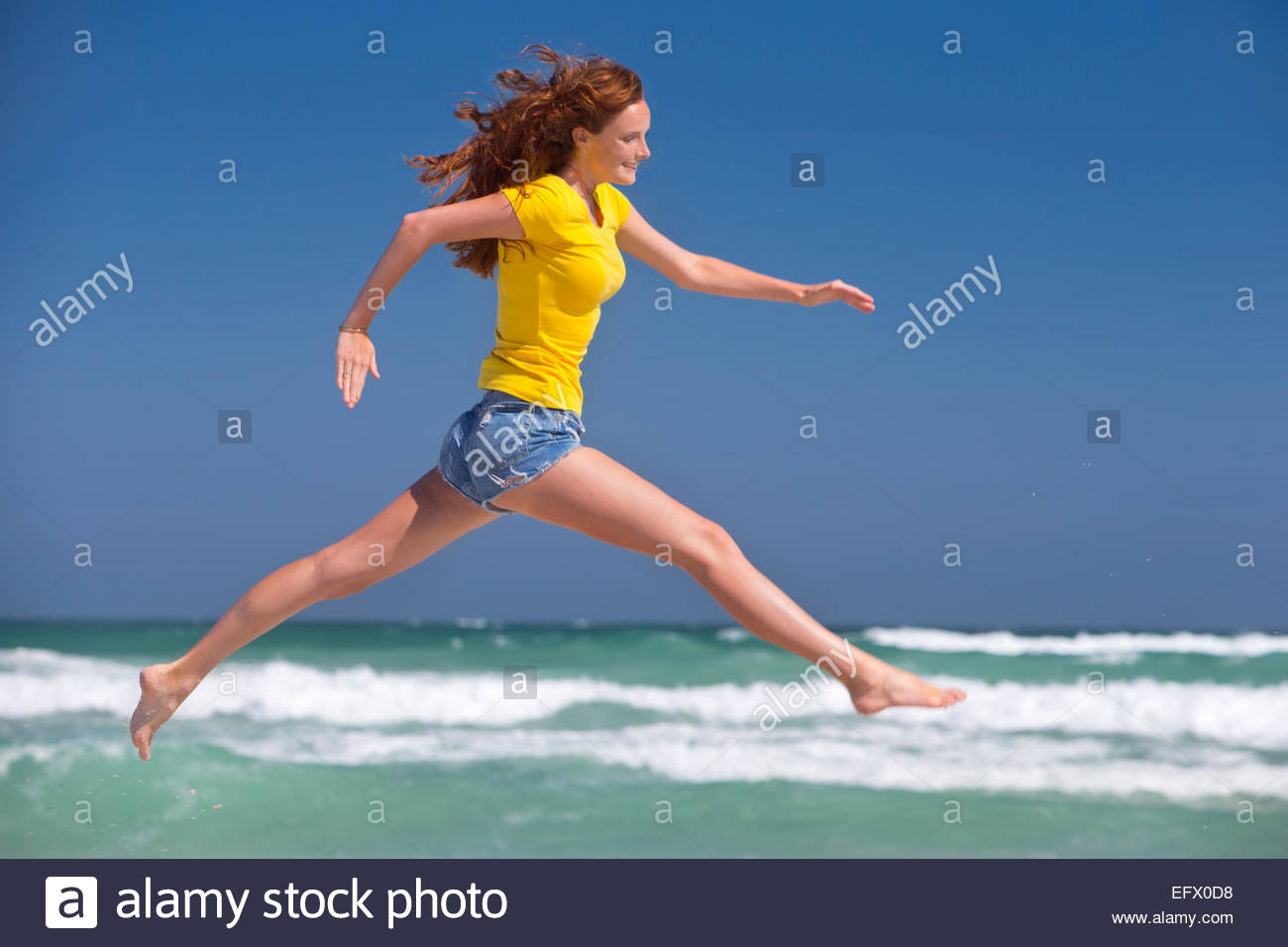 Happy woman leaping in air on sunny beach Stock Photo