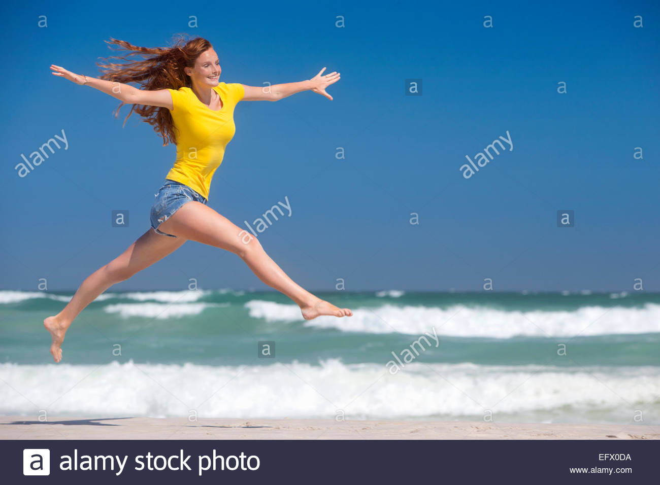 Happy woman leaping in air on sunny beach - Stock Image