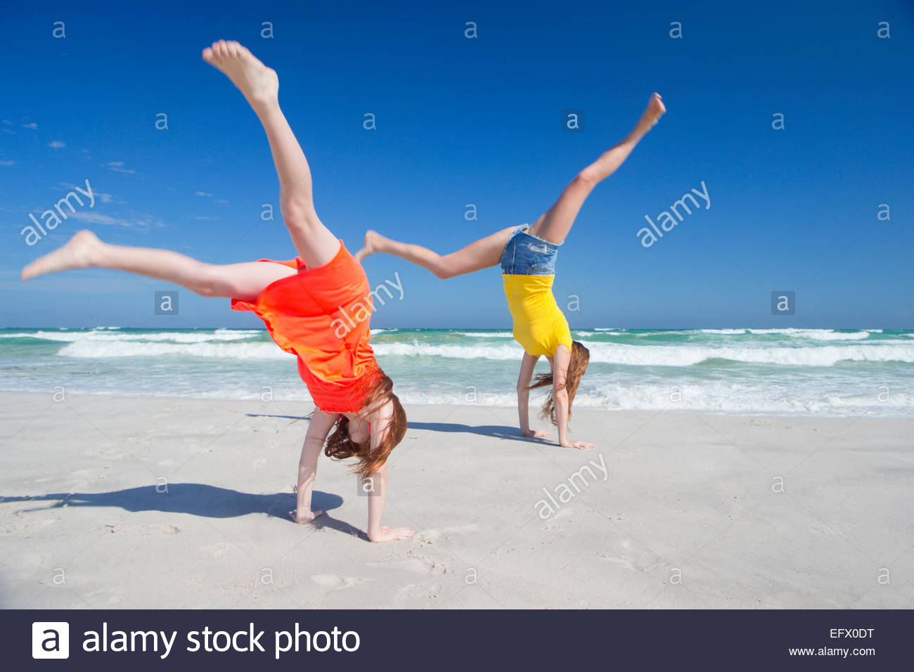 Mother and daughter cart wheeling on sunny beach - Stock Image