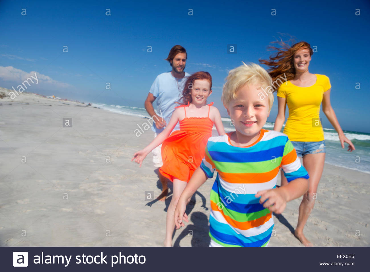 Happy family running toward camera, on sunny beach - Stock Image