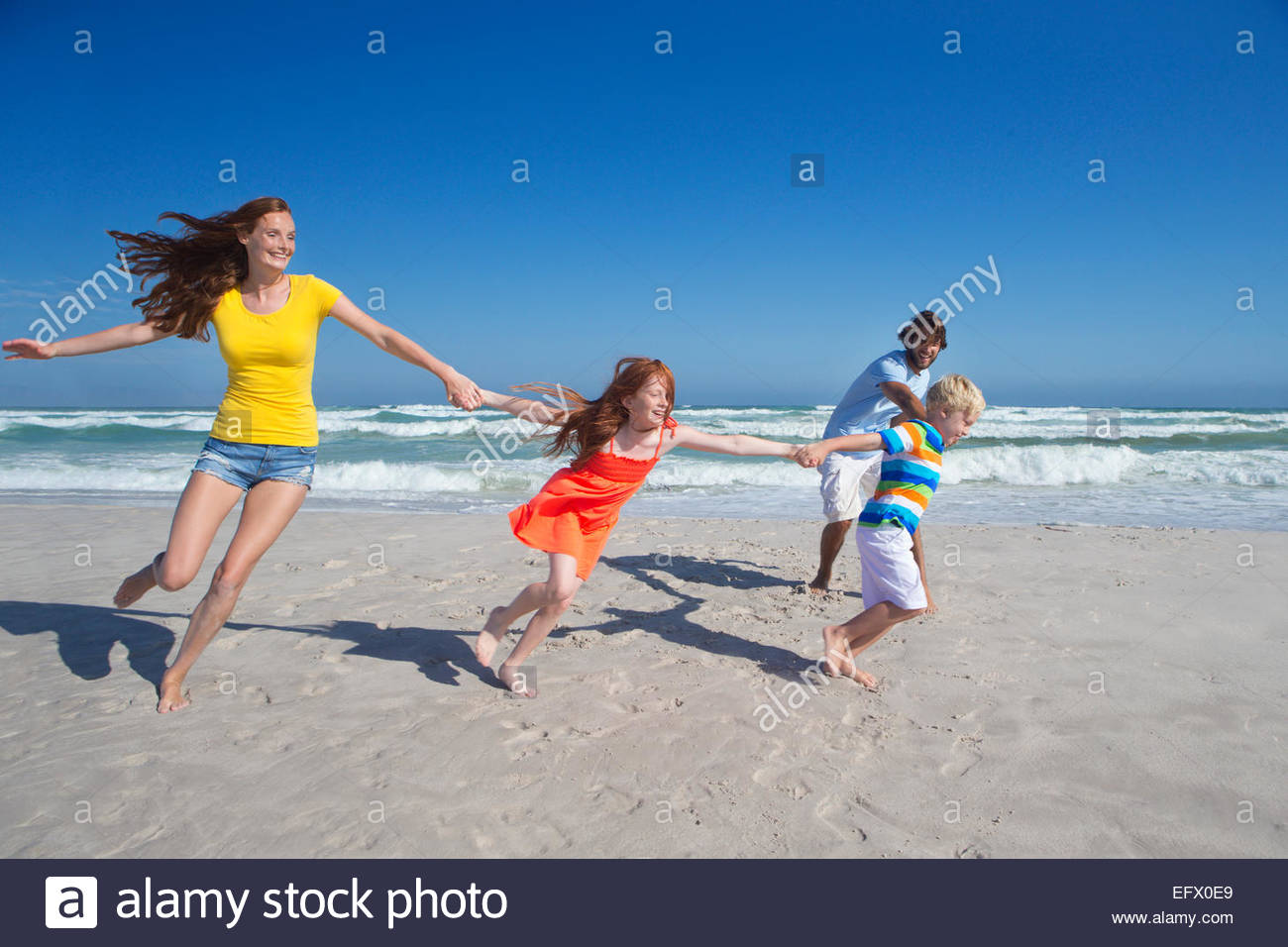 Happy family holding hands, running and pulling each other along sunny beach - Stock Image