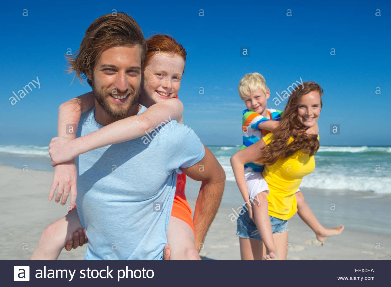 Mother and father, giving two children piggy back, on sunny beach - Stock Image