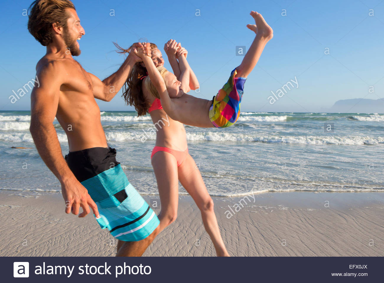 Happy couple swinging son in the air on sunny beach - Stock Image