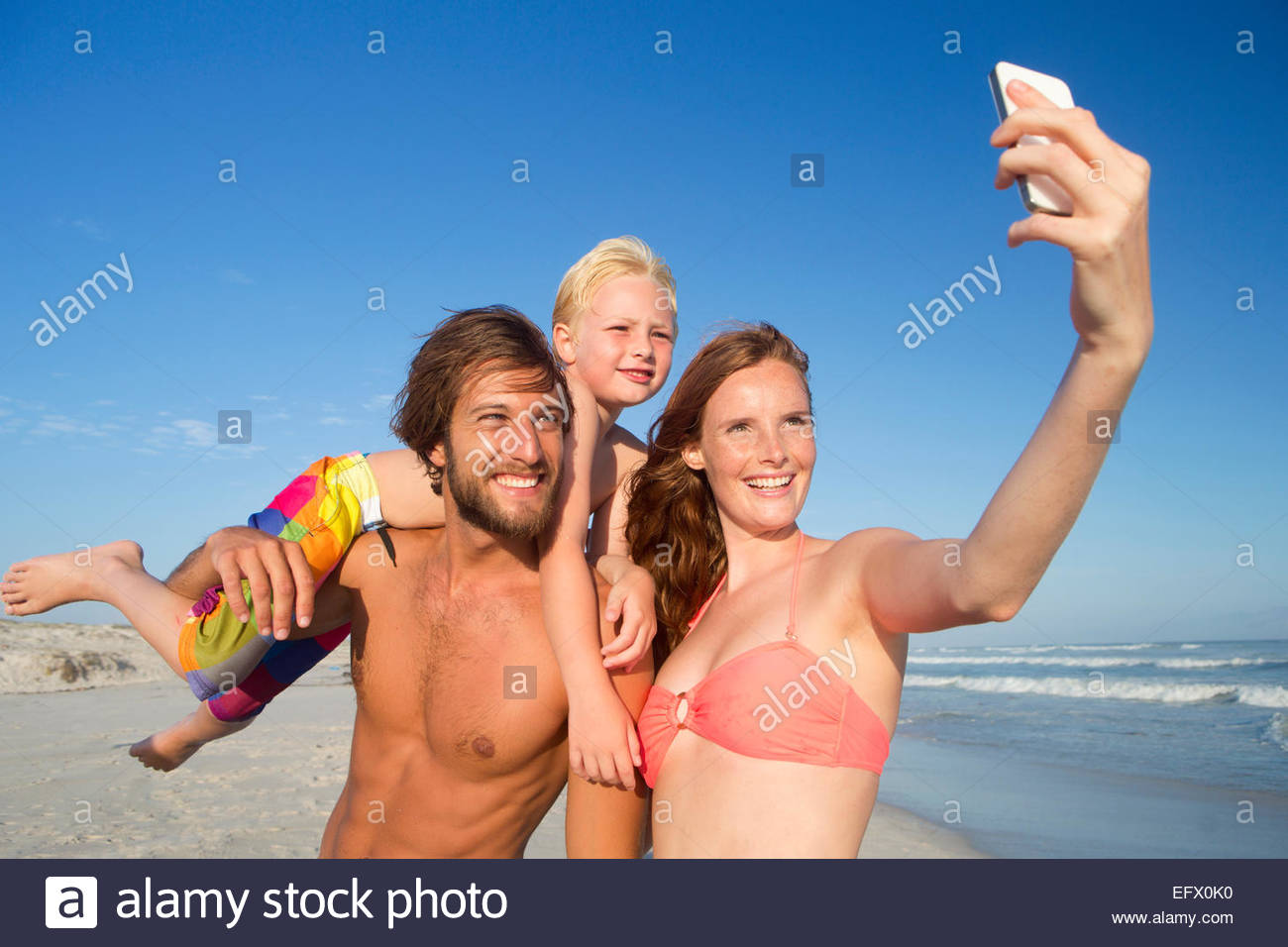 Portrait of happy couple with son on shoulder, taking selfie on sunny beach - Stock Image