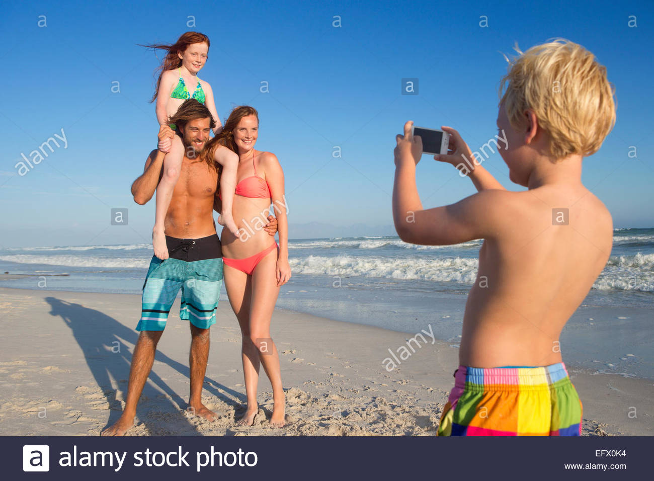 Boy taking photo of mother, father and sister on sunny beach - Stock Image