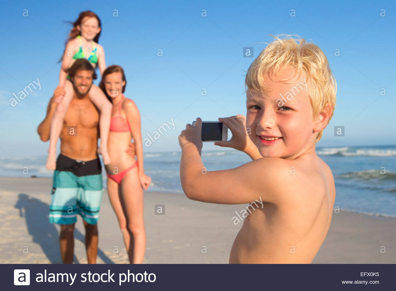 Boy, smiling at camera, taking photo of family on sunny beach - Stock Image