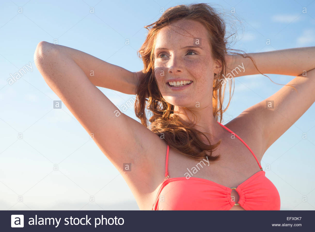 Smiling woman, with arms raised behind head, on sunny beach Stock Photo