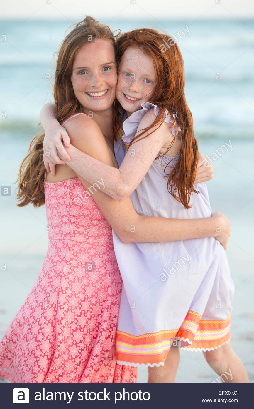 Portrait of mother and daughter, smiling at camera, embracing on sunny beach - Stock Image