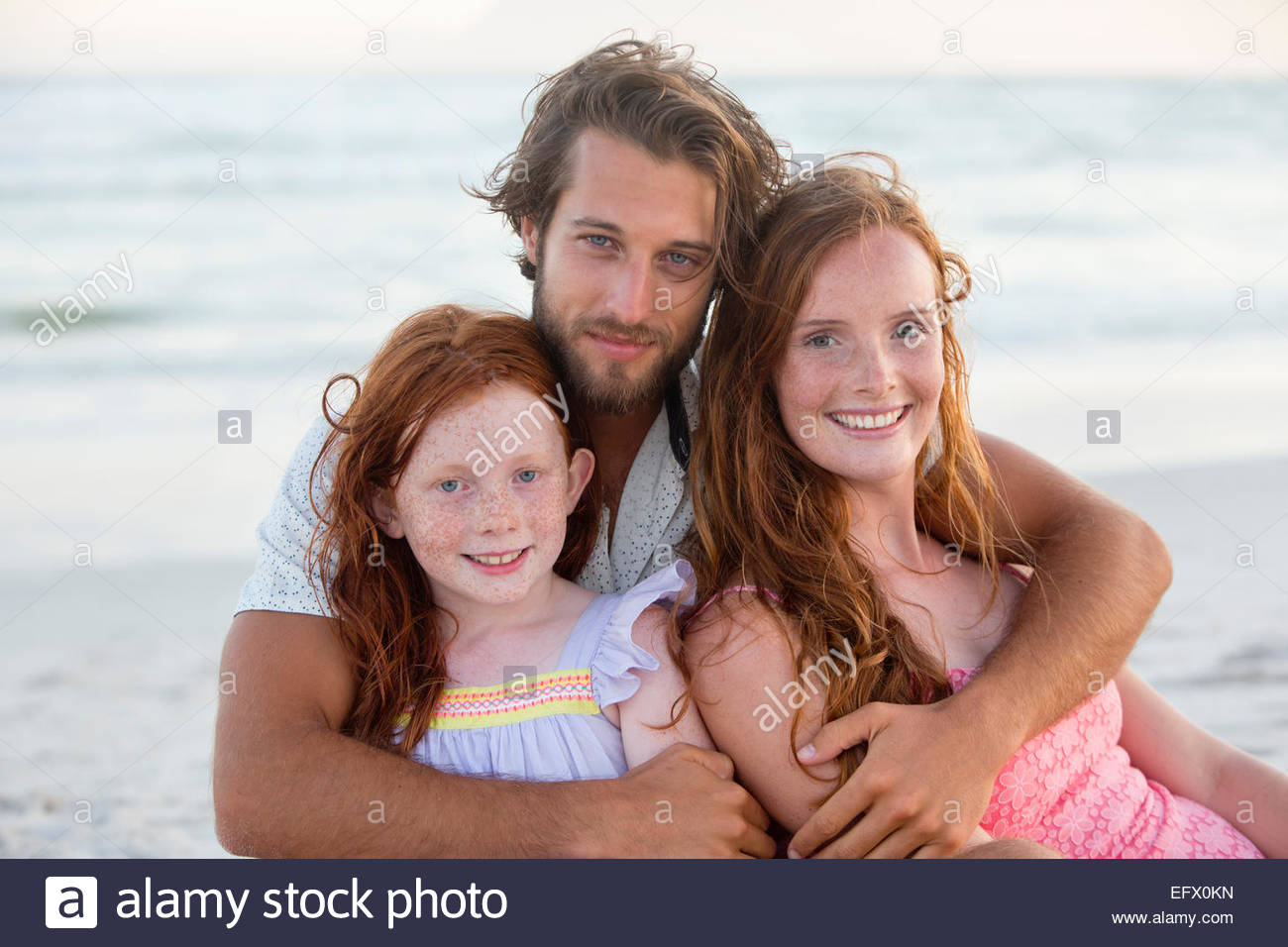 Portrait of family, smiling at camera, embracing on sunny beach - Stock Image