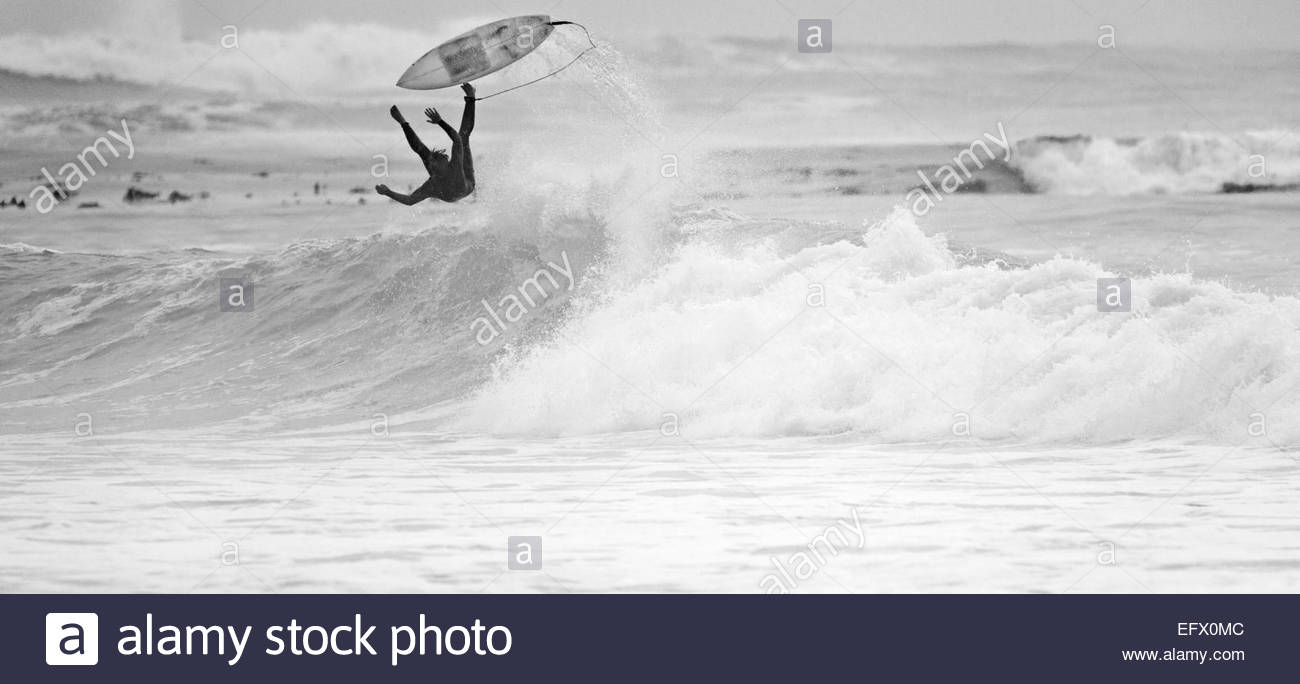 Surfer falling off surfboard on wave - Stock Image