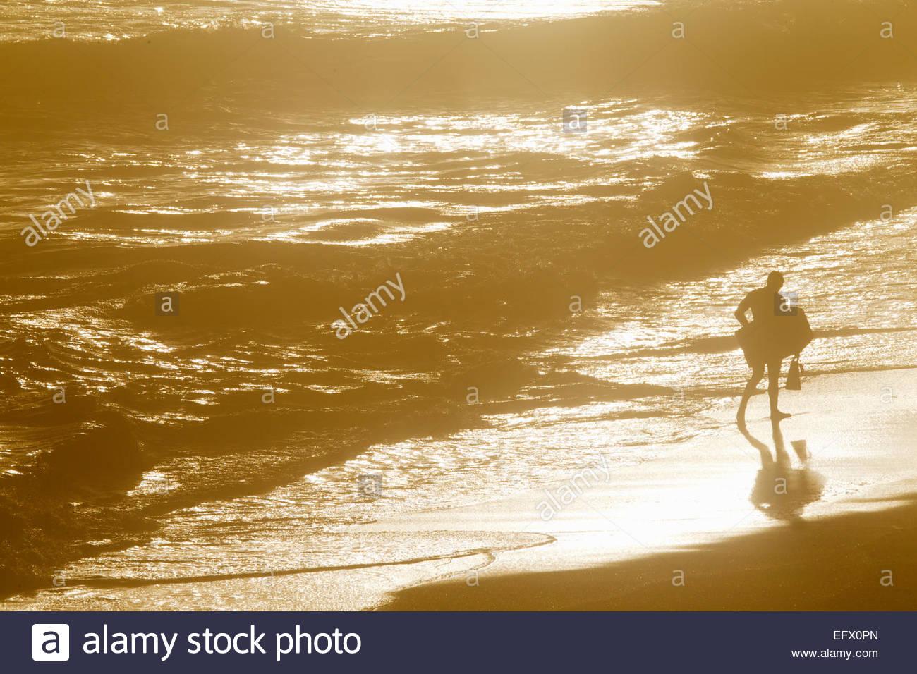 Man holding body board walking along beach through waves - Stock Image