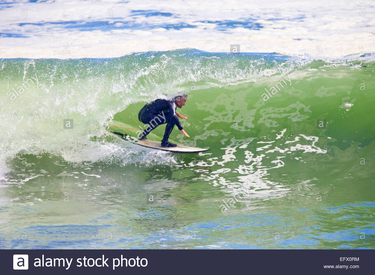 Surfer riding the curve of large wave - Stock Image