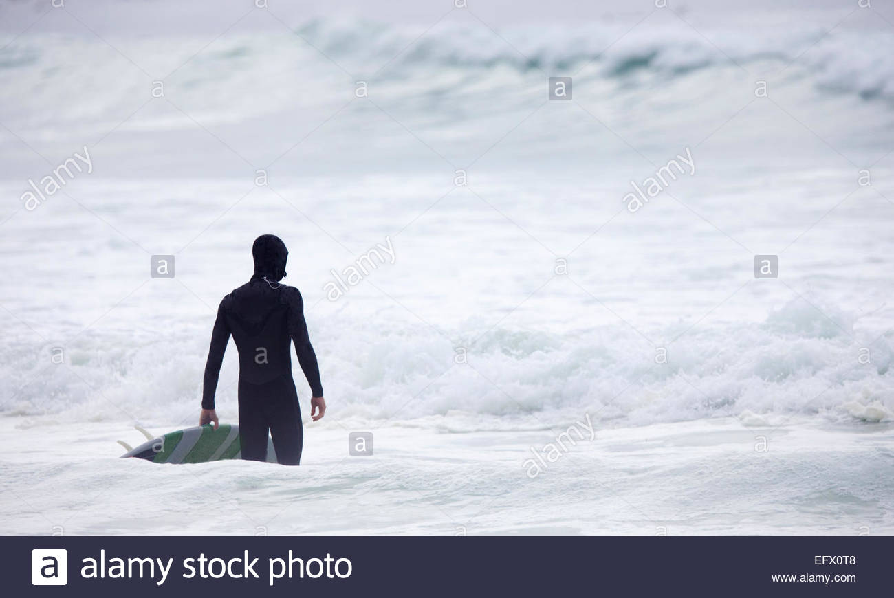 Man holding surfboard looking out to sea - Stock Image