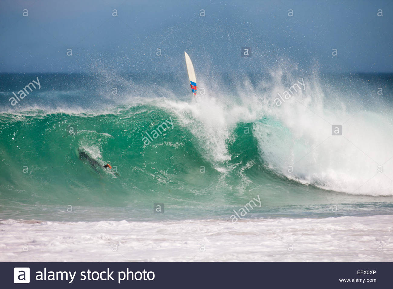 Loose surfboard on large wave - Stock Image