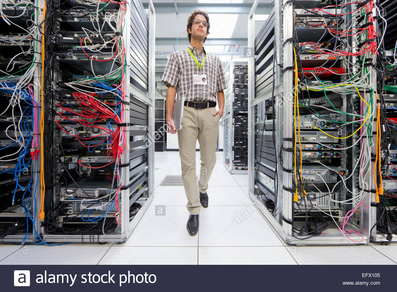 Technician walking through server room of data center Stock Photo
